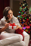 Happy young woman near christmas tree holding present box Royalty Free Stock Images