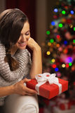 Happy young woman near christmas tree holding present box Royalty Free Stock Photography