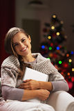 Happy young woman near christmas tree hugging tablet pc Stock Photography