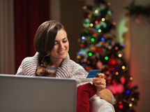 Happy young woman near christmas tree making online shopping Royalty Free Stock Images