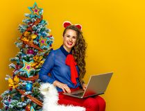 Happy young woman near Christmas tree sitting with laptop. Festive season. happy young woman near Christmas tree isolated on yellow background sitting with Royalty Free Stock Photos