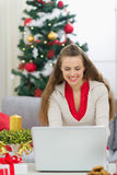 Happy young woman near Christmas tree using laptop Royalty Free Stock Photos