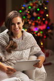 Happy young woman near christmas tree using tablet pc Royalty Free Stock Photos