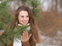 Happy young woman near fir-tree looking on copy space Royalty Free Stock Photography