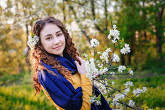 Happy young woman near a flowering tree in the Park.  Royalty Free Stock Images