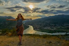 Happy young woman near Jvari Monastery of Georgia. Happy young woman waving hair and hands near windy Jvari Monastery of Georgia, overlooking Mtsheta town and Stock Photos