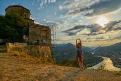 Happy young woman near Jvari Monastery of Georgia. Happy young woman waving hair and hands near windy Jvari Monastery of Georgia, overlooking Mtsheta town and Stock Photography