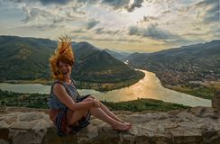 Happy young woman near Jvari Monastery of Georgia. Happy young woman waving hair and hands near windy Jvari Monastery of Georgia, overlooking Mtsheta town and Stock Photo