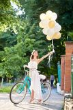 Happy young woman near vintage bicycle holding air balloons. Happy young woman near vintage bicycle over city background and holding air balloons of tender Stock Photography