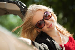 Happy young woman with a new convertible. Happy young blond with a new convertible car Stock Image