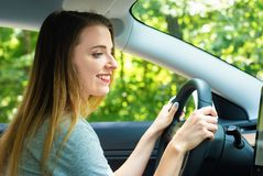 Happy young woman in a new car stock photography