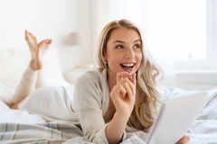 Happy young woman with notebook in bed at home Stock Image