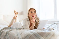 Happy young woman with notebook in bed at home Stock Images