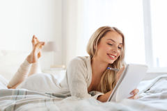 Happy young woman with notebook in bed at home Royalty Free Stock Photo
