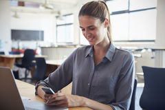 Happy young woman in office using smartphone Royalty Free Stock Photos