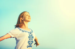 Happy young woman open her arms to the sky stock photo
