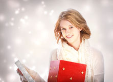 Happy young woman opening a big red gift box Royalty Free Stock Photography