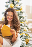 Happy young woman opening christmas letter near christmas tree Royalty Free Stock Photos