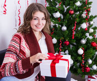 Happy young woman opening gift box near christmas tree Royalty Free Stock Photography