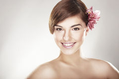 Happy young woman with orchid. On light background Royalty Free Stock Photo