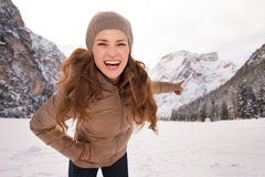 Happy young woman outdoors pointing on snow-capped mountains Stock Images