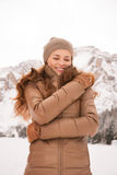 Happy young woman outdoors among snow-capped mountains Stock Photos