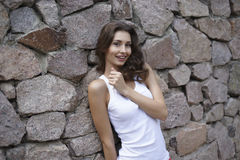 Happy young woman outdoors. Happy young woman at the wall outdoors Royalty Free Stock Image