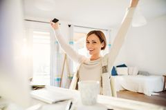 A happy young woman with outstretchced arms indoors, working in a home office. royalty free stock image