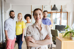 Happy young woman over creative team in office Stock Photo