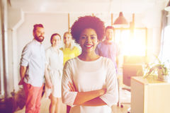 Happy young woman over creative team in office. Business, startup, people and teamwork concept - happy young women over creative team in office Stock Images