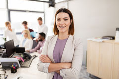 Happy young woman over creative team in office Stock Photography