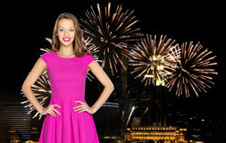 Happy young woman over firework at night city Stock Photo