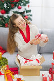 Happy young woman packing Christmas present parcel Royalty Free Stock Photo