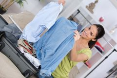 Happy young woman packing suitcase for travel Stock Photos
