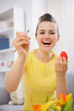 Happy young woman painting Easter eggs Stock Photography
