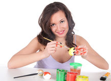 Happy young woman painting Easter eggs Royalty Free Stock Image
