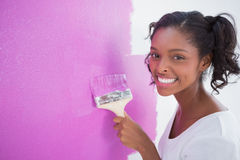 Happy young woman painting her wall in pink Royalty Free Stock Photography