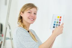 Happy young woman before painting wall stock photo