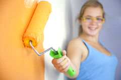 Happy young woman painting wall Stock Photos