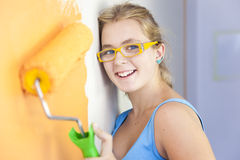 Happy young woman painting a wall. In her room/  colorful life / real view Royalty Free Stock Photos