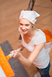 Happy young woman painting a wall in orange color Royalty Free Stock Photos