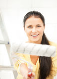 Happy young woman with paintroller. Picture of happy young woman with paintroller Royalty Free Stock Photos