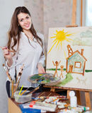 Happy young woman paints on canvas with oil paints Stock Images
