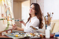 Happy young woman paints  on canvas Royalty Free Stock Images