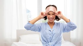Happy young woman in pajama and eye sleeping mask royalty free stock image