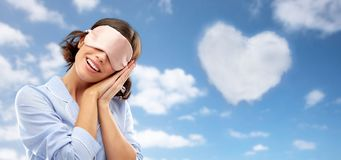 Happy young woman in pajama and eye sleeping mask royalty free stock photography
