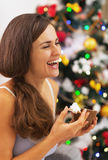 Happy young woman in pajamas having snack near christmas tree Stock Photo