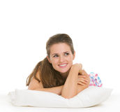 Happy young woman in pajamas laying on pillow Stock Photos
