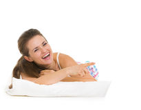 Happy young woman in pajamas laying on pillow Stock Photo