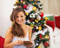 Happy young woman in pajamas near christmas tree drinking hot be Stock Photos